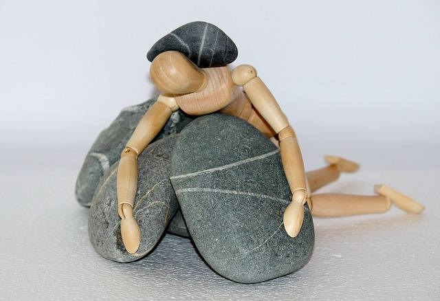 Wooden figure under stones representing someone who feels stuck